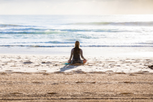 woman sitting on beach meditating